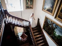 Bride descends stairs at Smedmore House